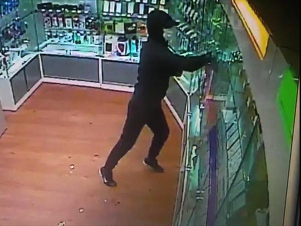 Видео: Небрежный налетчик в маске унес из салона на Пискаревском четыре коробки, а в них — муляжи
