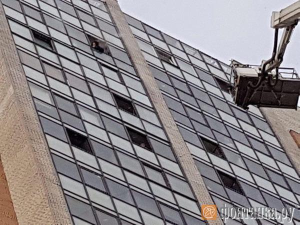 В горящем доме на Коломяжском пытаются снять жильца с 23-го этажа
