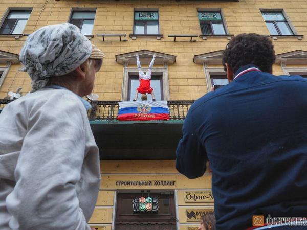 На балконе на Невском в стойке на руках завис футболист